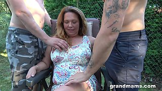 Husband is watching his mature wife fucking two horny young dudes in the garden