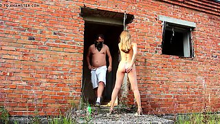 Submissive blonde on a leash gets spanked and fisted outside