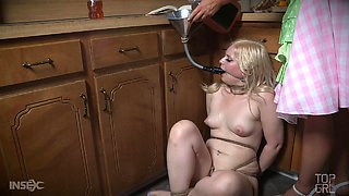 Housewife abuses a submissive beauty in her kitchen